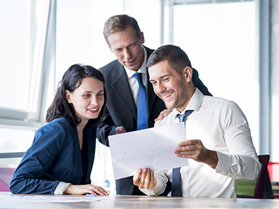 Three business people looking at paper and smiling