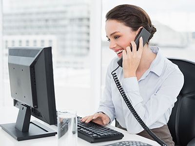 Business woman smiling on phone, happy to learn she can replace commercial landlines with a VoIP phone system